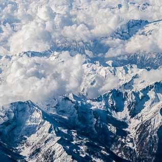 Luftaufnahme der Alpen, schneebedeckte Gipfel mit Wolken