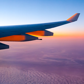 view from an airplane of the dawn with an A330 wing