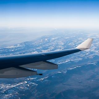 Blick aus dem Flugzeug mit Tragfläche auf das Juragebirge aus nördlicher Richtung, dahinter (links über der Tragfläche) Bieler-, Murten- und Neuenburgersee