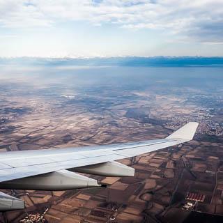 Blick über die Poebene zu den Alpen aus dem Flugzeug mit Tragfläche