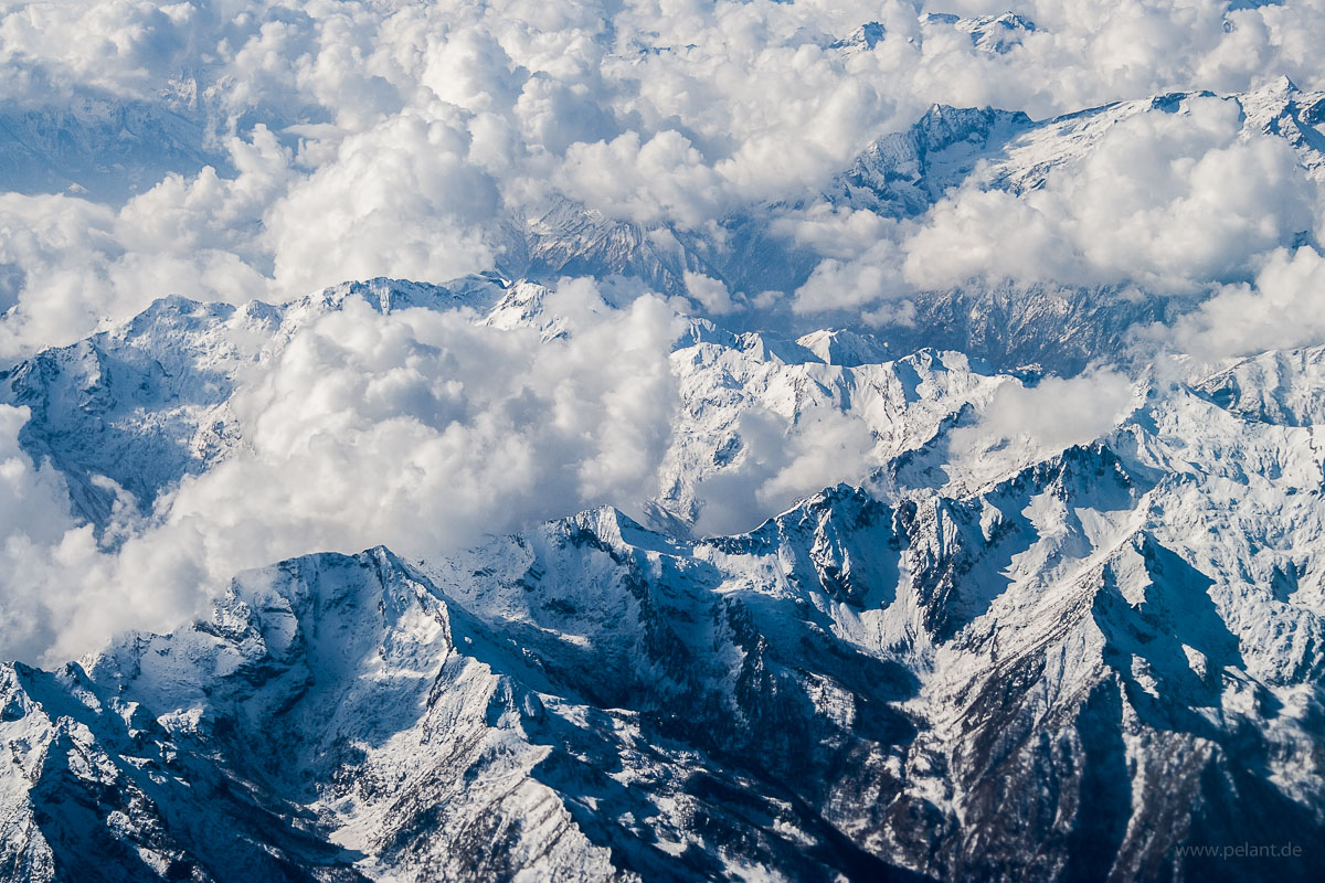 aerial view of the Alps mountains, snow covered summits with clouds