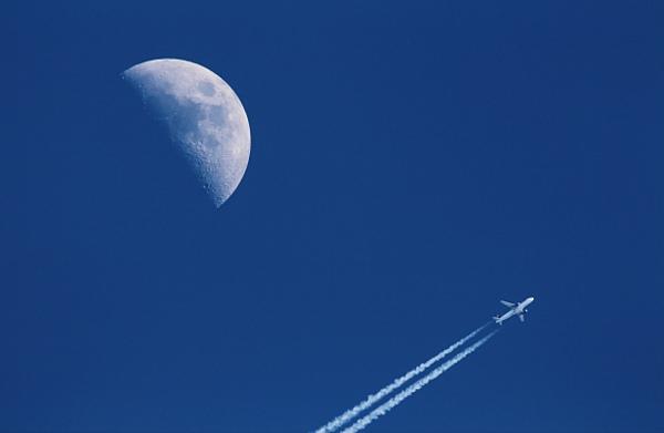 Mond und Flugzeug mit Kondensstreifen