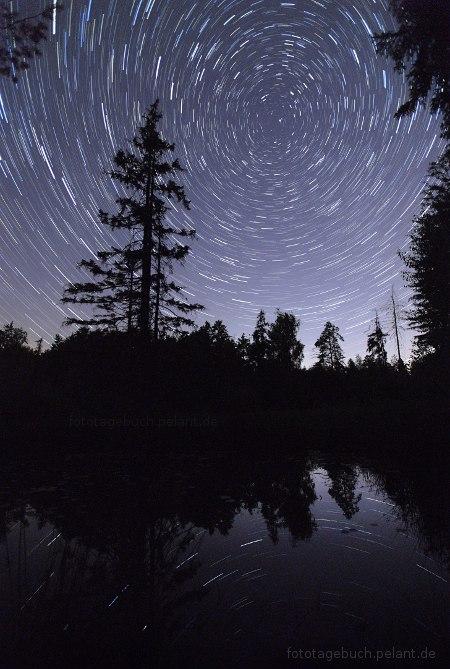 Sternspuren (Startrails) spiegeln sich im Birkensee bei Nacht. Im Zentrum der Rotation ist der Polarstern.