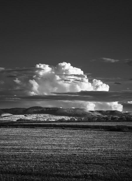Wolken türmen sich über der Schwäbischen Alb, davor abgeerntetes Feld bei Einsiedel. (Links der Rossberg mit Rossbergturm.) Schwarzweiß-Infrarot.