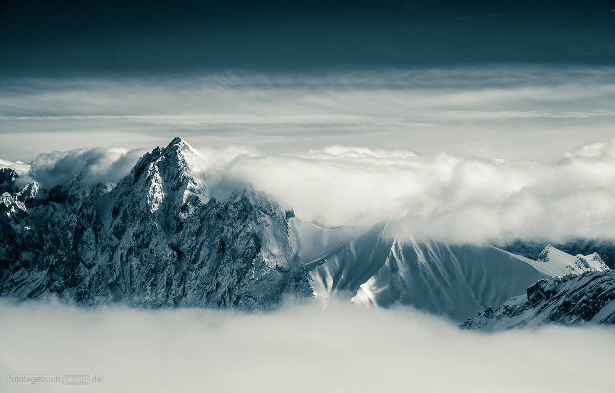 mountains between clouds