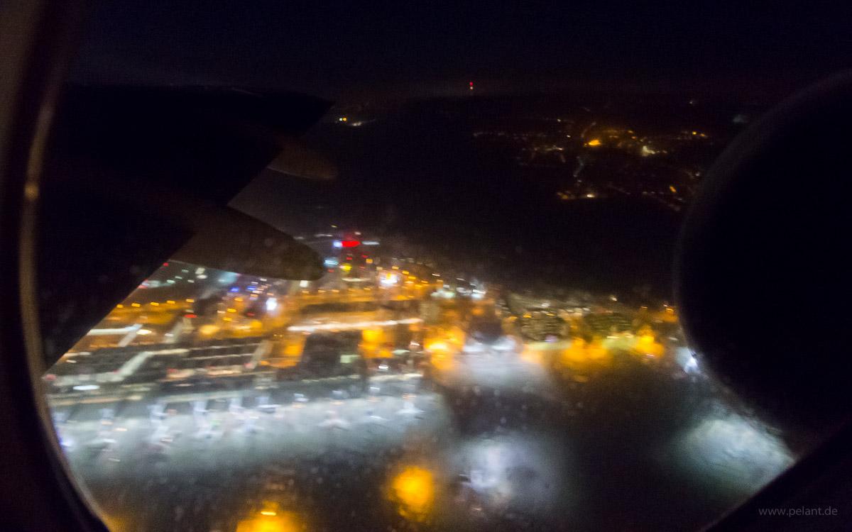 Blick auf den Stuttgarter Flughafen während dem Start durch das vom Enteisungsmittel außen verschmierte Flugzeugfenster
