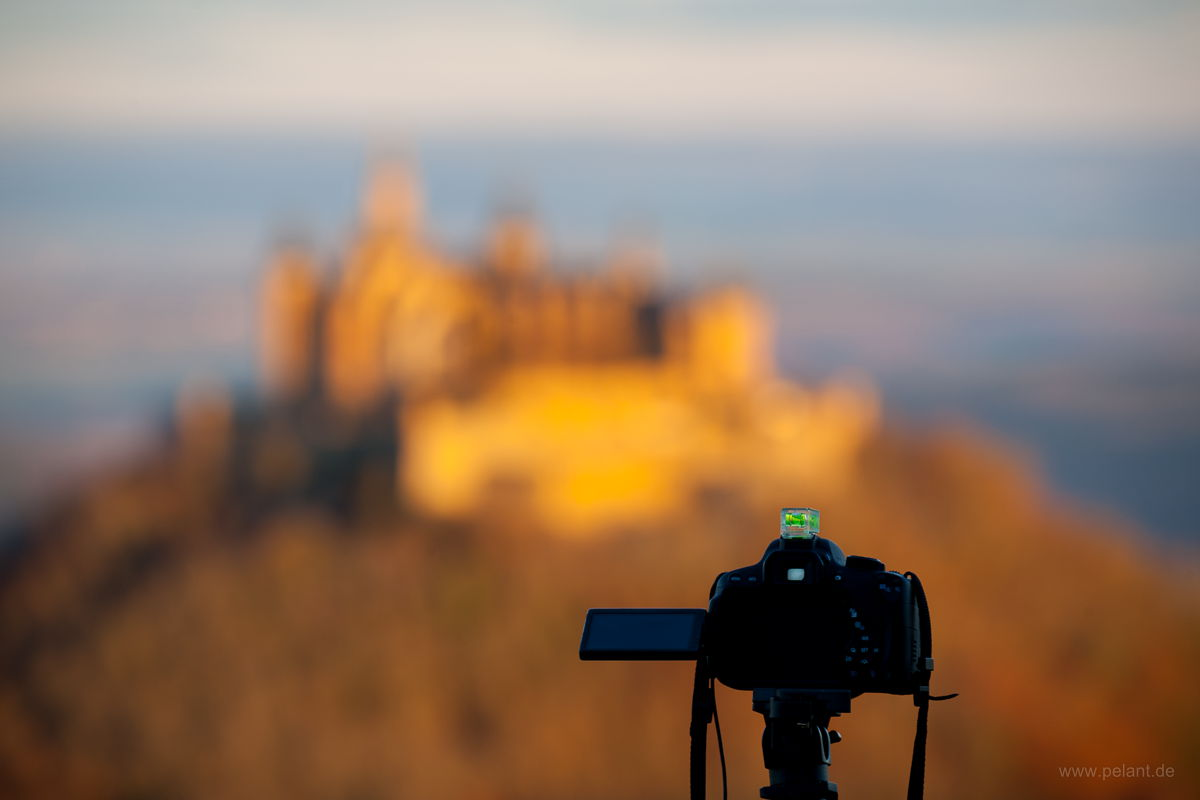 camera on a tripod in front of blurred Hohenzollern castle in the morning light