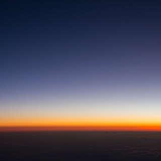 Abenddämmerung über den Wolken (Blick aus dem Flugzeugfenster)