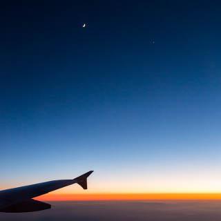 Mond und Venus (rechts) in der Abenddämmerung über den Wolken (Blick aus dem Flugzeug, Luftaufnahme)