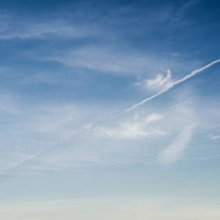 Ein diagonal durch das Bild verlaufender Kondensstreifen wirft einen Schatten