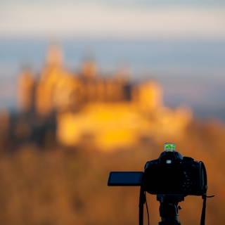 Kamera auf einem Stativ, dahinter (unscharf) die Burg Hohenzollern im Morgenlicht