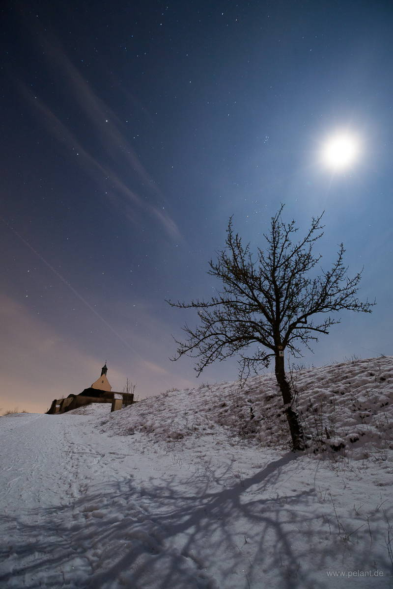 view of the Wurmlinger chapel at night in winter with snow and stars in the sky