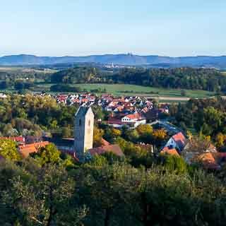 Blick auf Neckartailfingen mit dem schiefen Turm der Martinskirche und über das Neckartal mit dem Albtrauf im Hintergrund