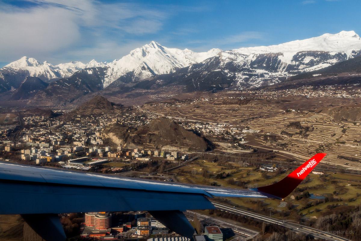 Luftaufnahme von Sitten (Sion) während dem Landeanflug auf RWY 25 des Flughafens Sitten (SIR) von Zürich mit Helvetic Airways. Die Tragfläche ist auch im Bild.