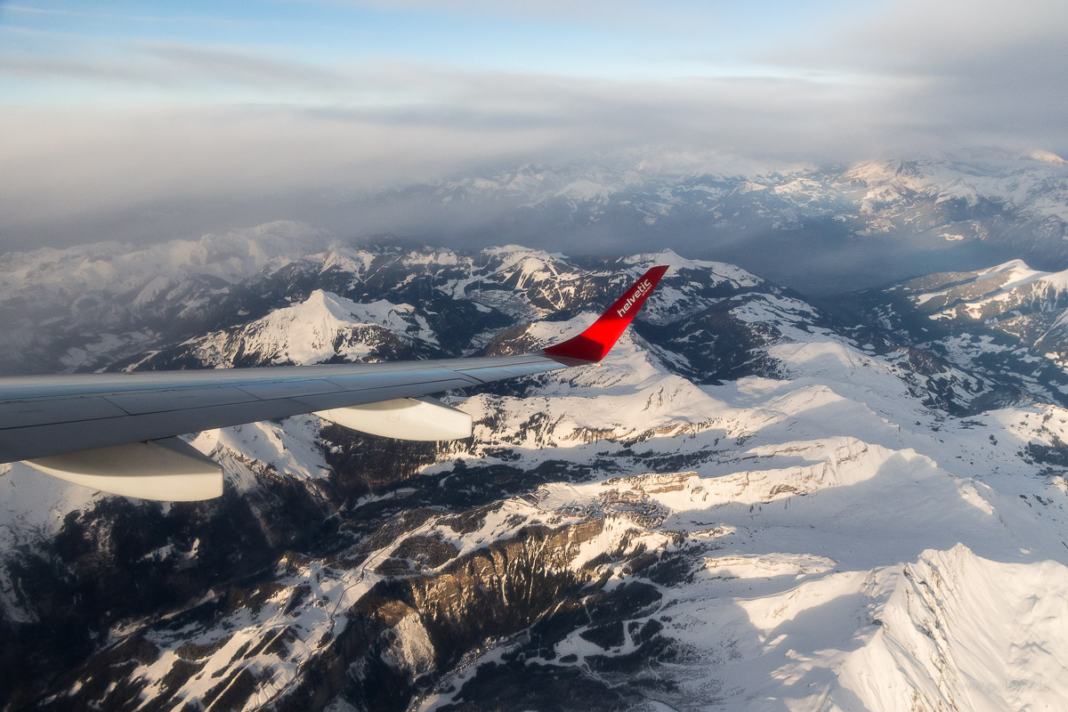 aerial view of snow-covered Chablais Alps in winter, viewed from Helvetic Airways Embraer 190 airplane during short flight from Sion to Zuerich