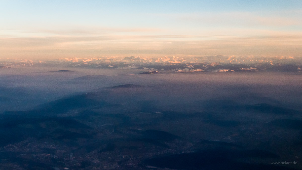 aerial view of the Alps in the evening light with fog in front of them
