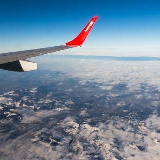 Blick aus dem Flugzeug über der Schweiz auf aufklarende Bewölkung