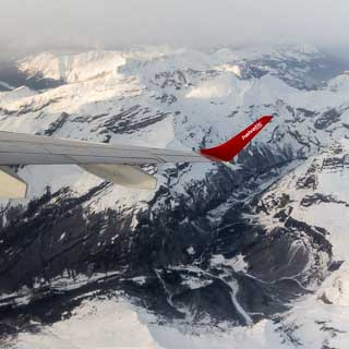 aerial view of Cirque du Fer à Cheval in winter with winglet of Helvetic Airways Embraer 190