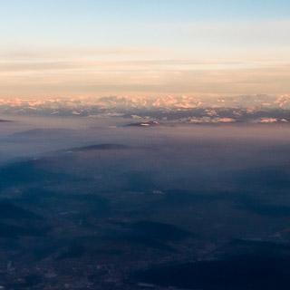 Luftbild vom Alpenkamm im Abendlicht mit Nebel über dem Vorland