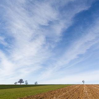Wolken einer Warmfront im Frühling über den Feldern